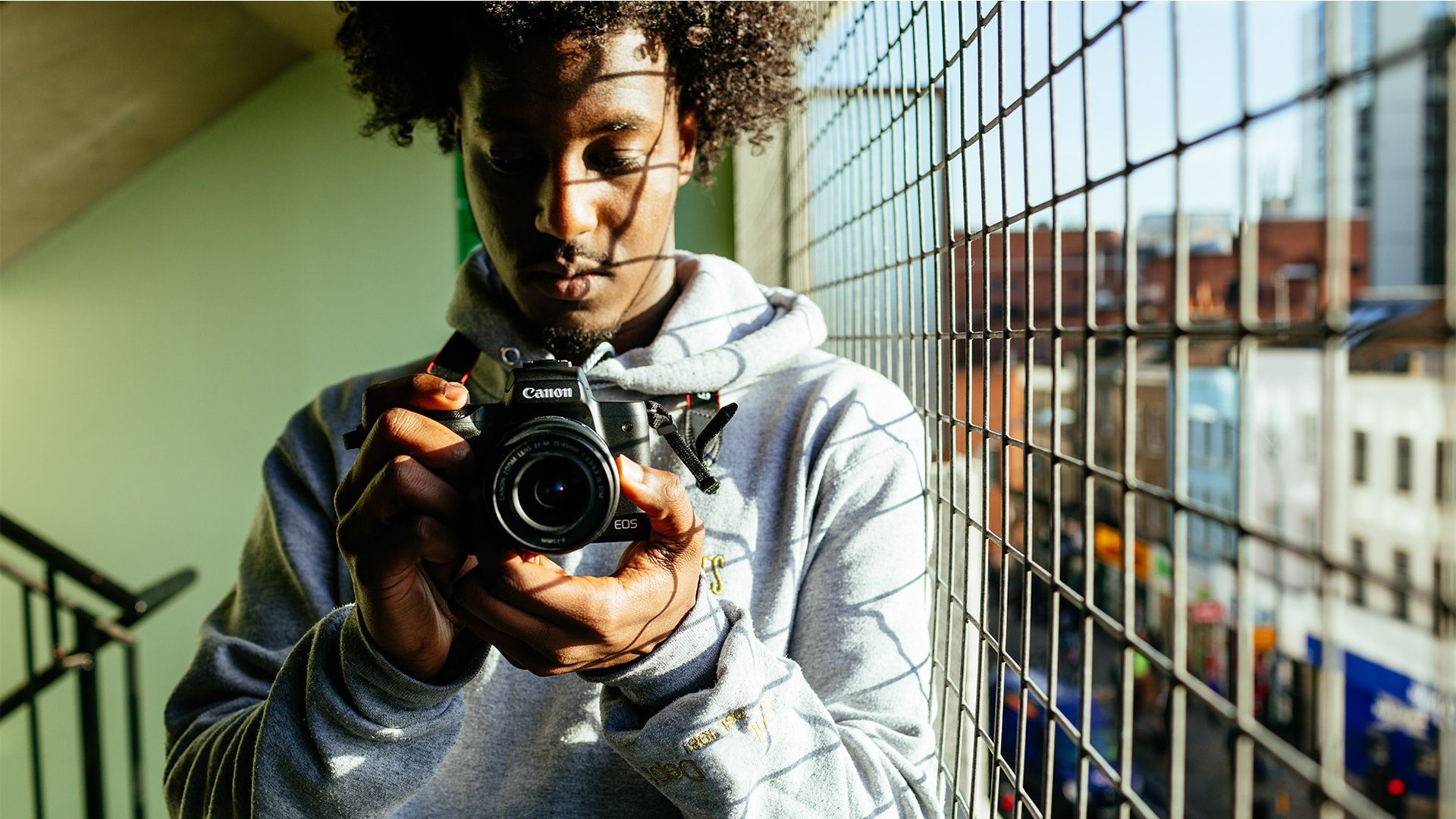A man holds a Canon camera.